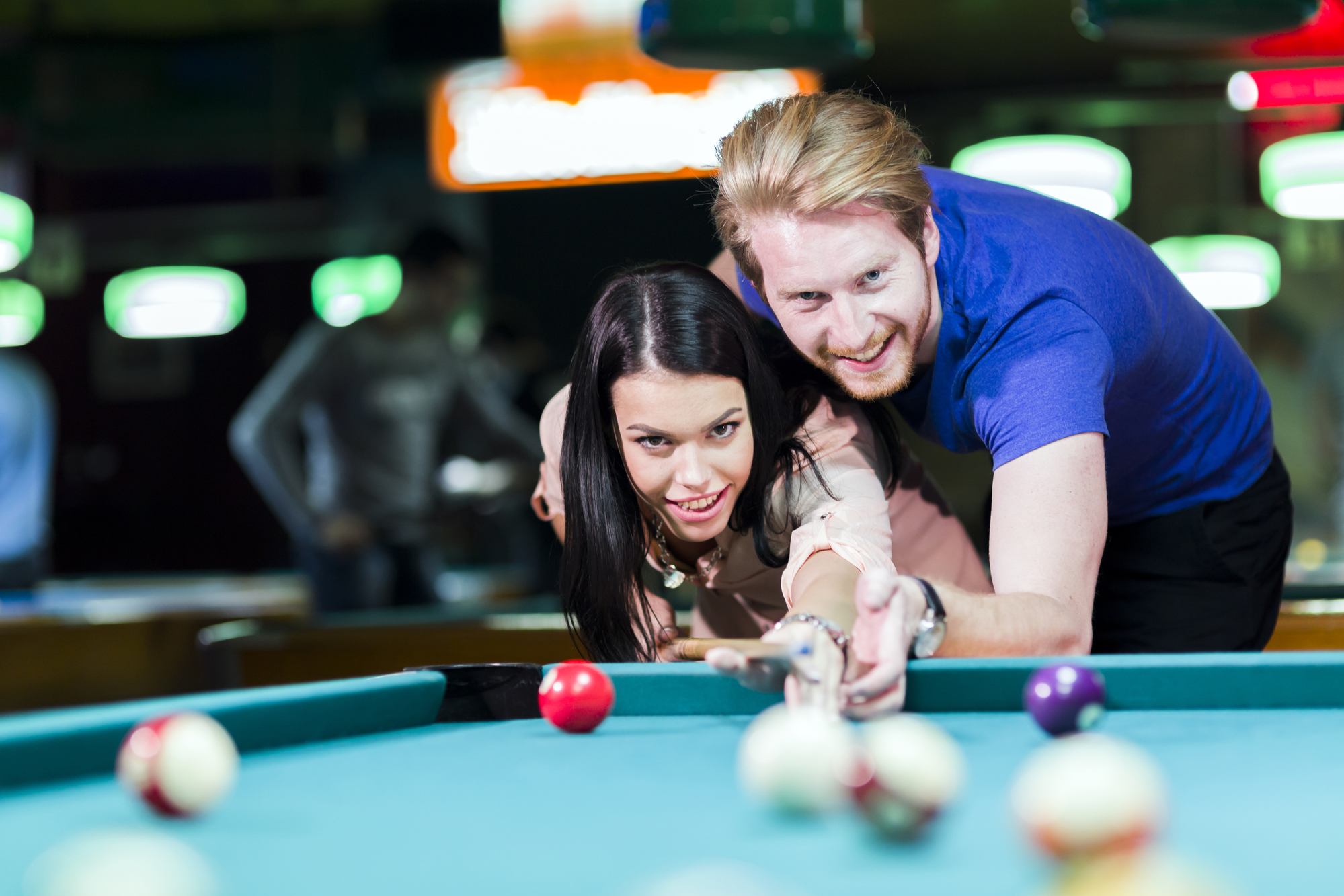 Young handsome man and woman flirting while playing billiards